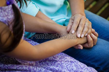 midsection of senior woman holding hands