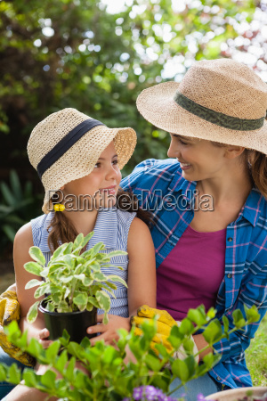 smiling mother with daughter holding potted