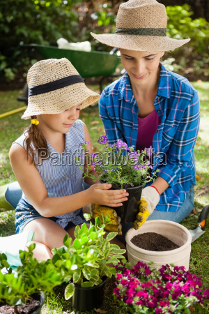 smiling mother and daughter holding potted