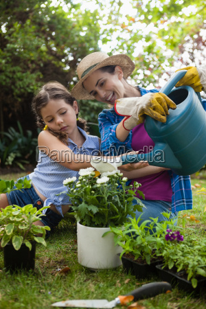 happy mother with daughter watering potted
