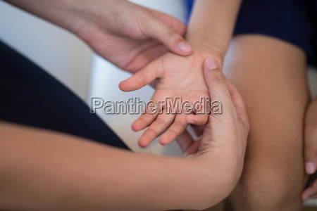 cropped hands of female therapist examining