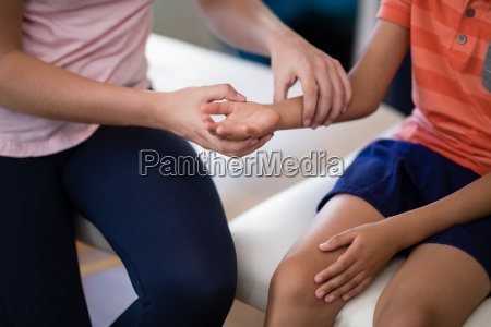 midsection of female therapist examining wrist
