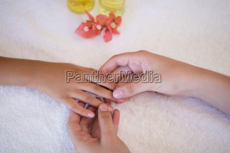 female therapist examining hand of boy