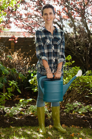 portrait of smiling woman holding watering