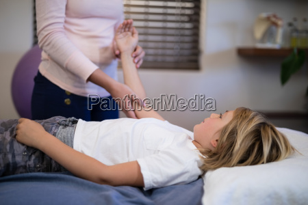 midsection of female therapist examining arm