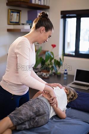 young female therapist examining boy lying