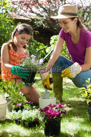 mother assisting daughter in gardening on