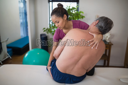 young female therapist examining buttocks of