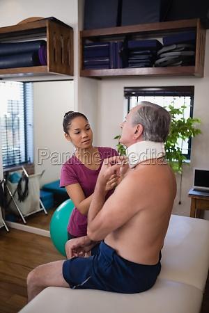 female therapist examining neck collar of