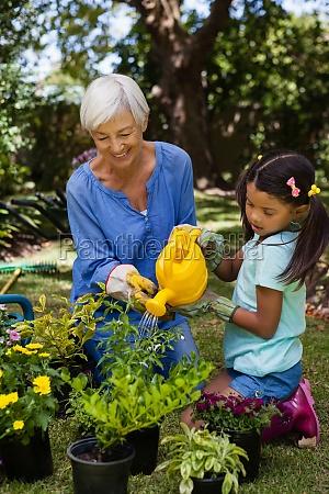 smiling senior woman and girl watering