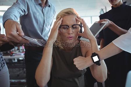 frustrierte geschaeftsfrau sitzt inmitten des teams