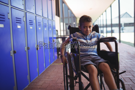 portrait of boy sitting on wheelchair