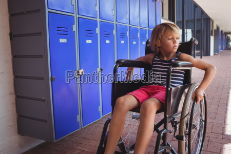 thoughtful student sitting on wheelchair in