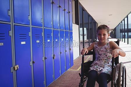 portrait of schoolgirl sitting on wheelchair
