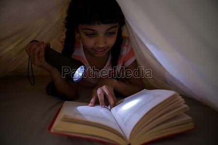maedchen haelt taschenlampe beim lesen roman