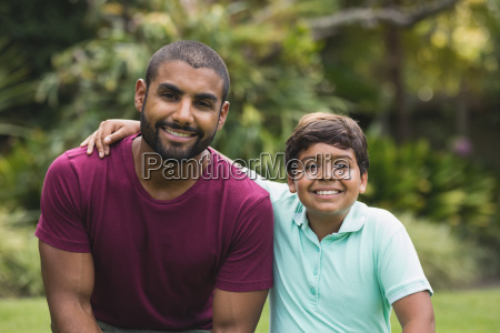 smiling father and son sitting at