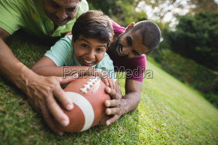 happy boy playing rugby with father