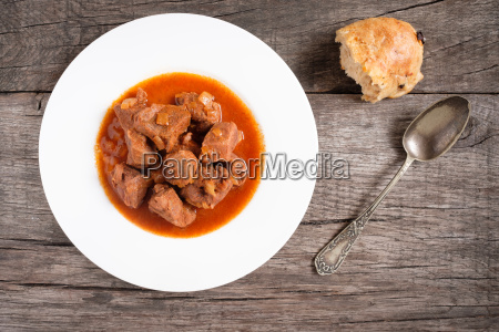 goulash with onions and bread in