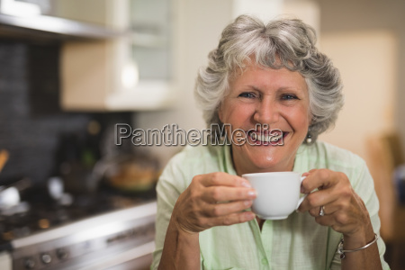 happy senior woman holding cup at