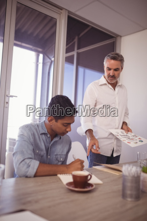businessman assisting young colleague in office