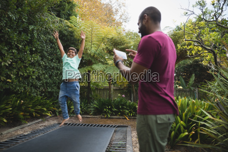 father photographing son while jumping on