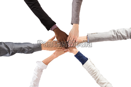 multi ethnic people stacking hands