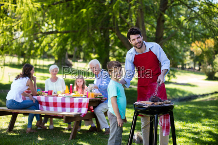 father and son barbequing in the
