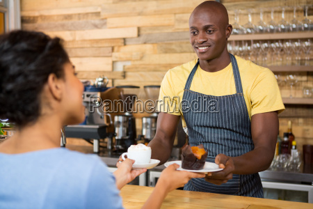 male barista serving coffee and dessert