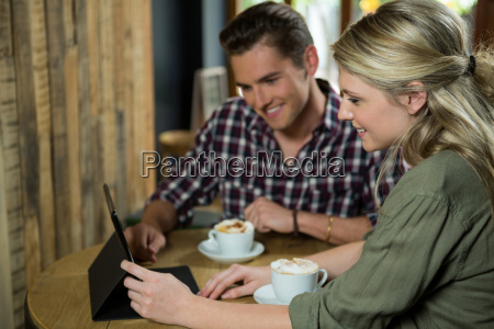 smiling couple using digital tablet at
