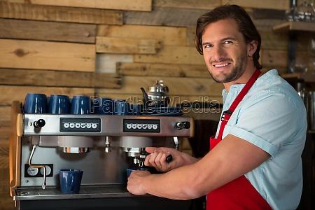 barista preparing coffee with machine in