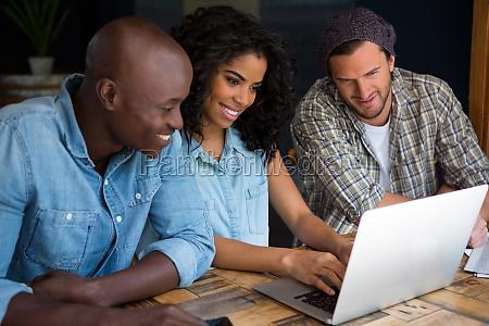 happy friends using laptop in coffee