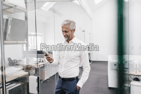 mature businessman holding cell phone in