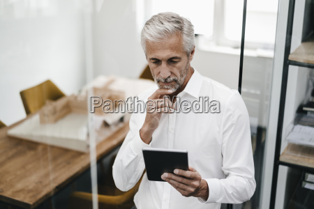 mature businessman looking at tablet in