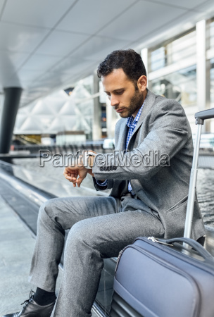 businessman checking the time in the