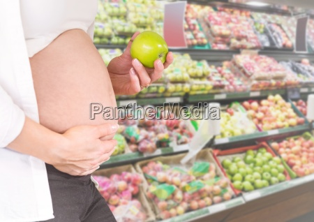 pregnant woman mid section holding apple