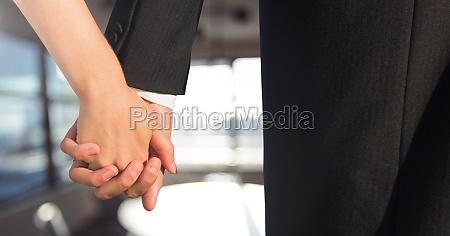 wedding couple holding hands near windows