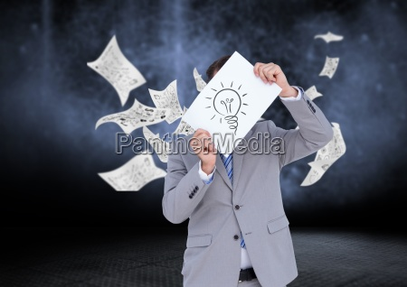 businessman holding sheet of paper showing
