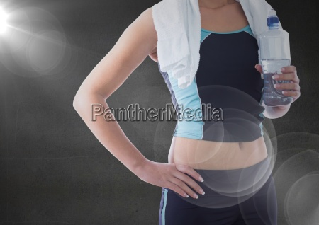 fit woman holding water bottle against