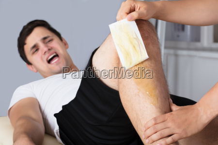 therapist waxing mans leg with wax