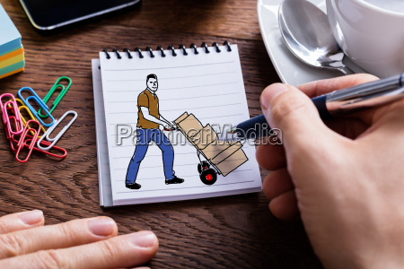 person hand holding pencil on notepad