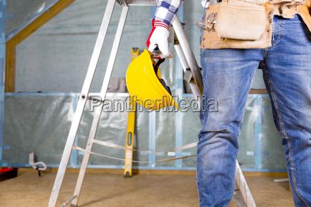 erbauerheimwerker mit gelbem schutzhelm und werkzeuggurt