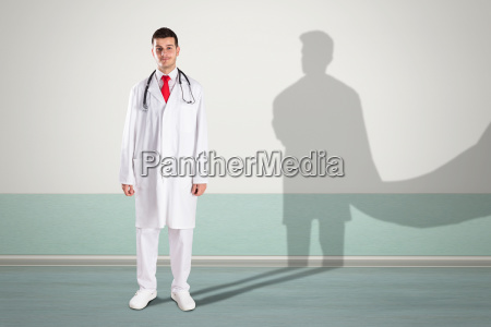 doctor with superhero shadow on wall
