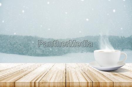 tasse kaffee auf holztisch mit winterschneefaellen