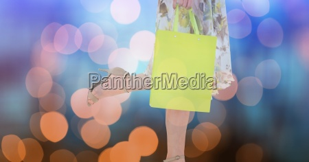 woman holding shopping bag over bokeh