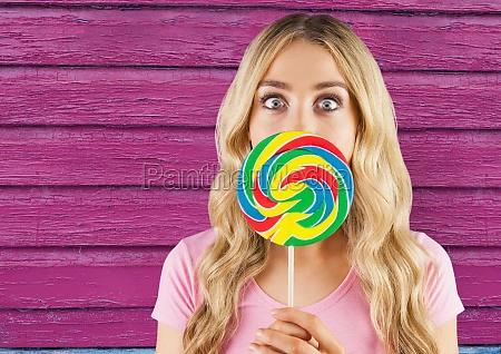 hipster mit lollipop mit rosa holzhintergrund