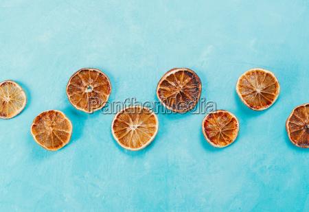 dried orange slices on blue concrete