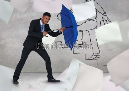 businessman holding blue umbrella amidst flying