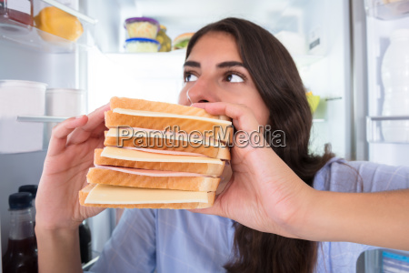 young woman eating sandwich