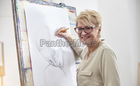 portrait smiling female artist sketching at