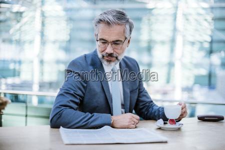 geschaeftsmann liest zeitung und trinkt kaffee
